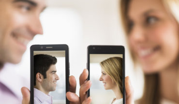 Couple holding smartphones with their pictures on